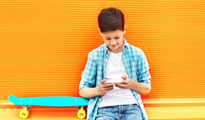 O menino do adolescente da forma usa o smartphone, skate em um colorido imagens de stock royalty free