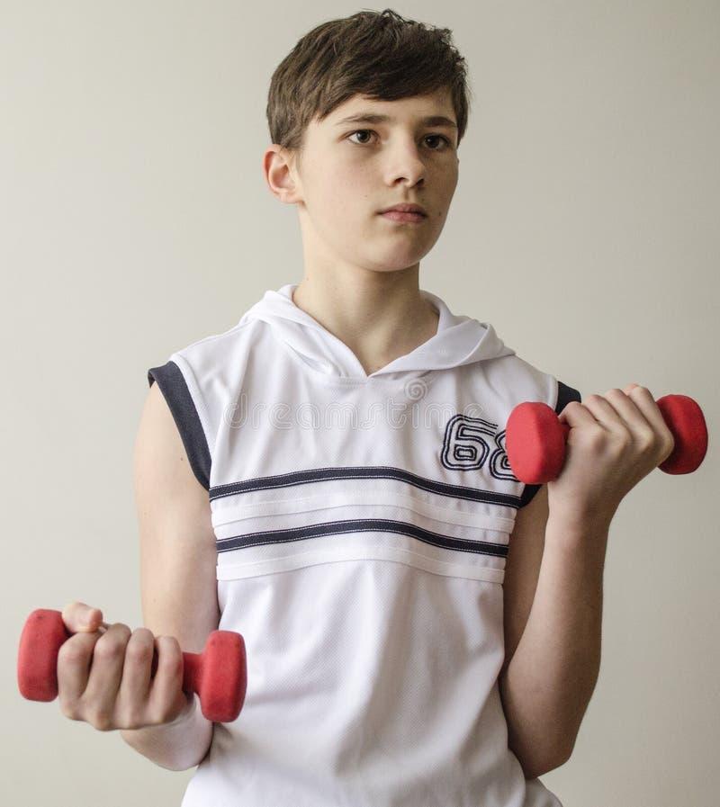 O menino do adolescente em uma camisa branca sem luvas está fazendo exercícios com pesos foto de stock