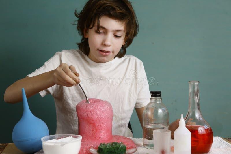 O menino do adolescente faz experiências químicas com reagente fotografia de stock royalty free