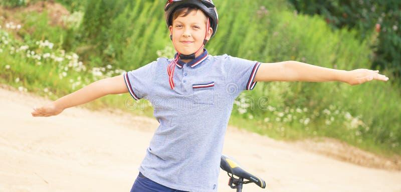 O menino do adolescente no capacete protetor espalhou seus braços para fora como uma posição do pássaro ao lado de sua bicicleta  fotos de stock royalty free