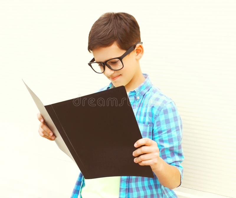O menino do adolescente nos monóculos está olhando ou livro de leitura no branco foto de stock