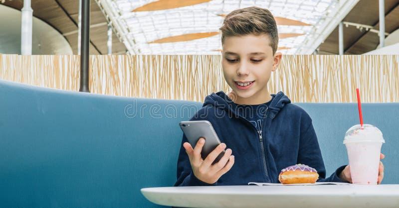 O menino do adolescente senta-se na tabela no café, bebe o milk shake, come a filhós, guarda o smartphone em sua mão O menino jog fotos de stock