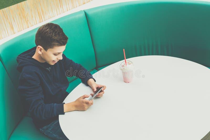 O menino do adolescente senta-se na tabela no café, bebe-se o milk shake e usa-se o smartphone O menino joga jogos no smartphone, imagens de stock royalty free