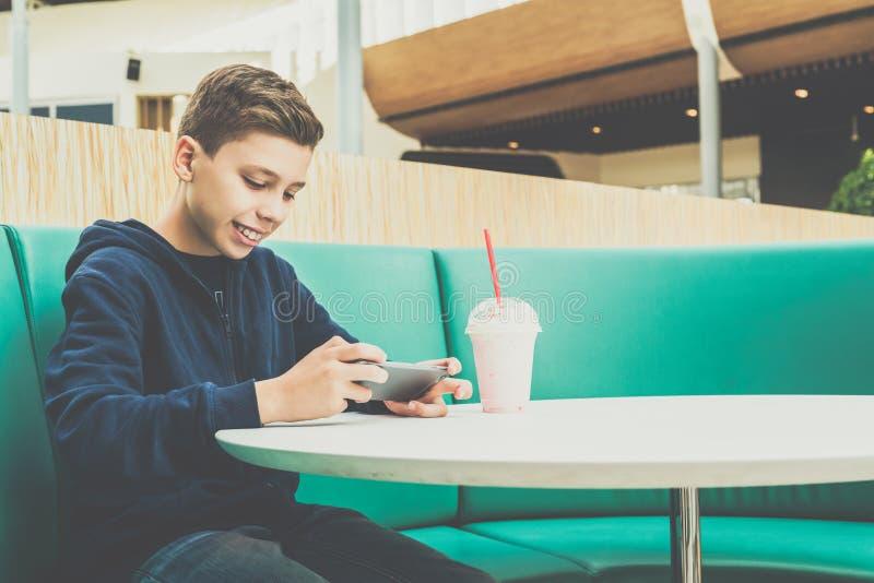 O menino do adolescente senta-se na tabela no café, bebe-se o milk shake e usa-se o smartphone O menino joga jogos no smartphone, fotografia de stock royalty free