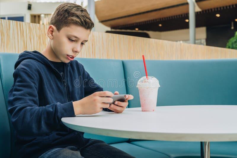 O menino do adolescente senta-se na tabela no café, bebe o milk shake, usa o smartphone O menino joga jogos no smartphone, consul imagens de stock royalty free