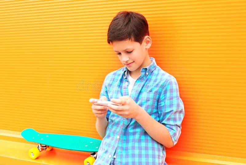 o menino do adolescente usa o smartphone, skate em uma laranja colorida imagem de stock royalty free