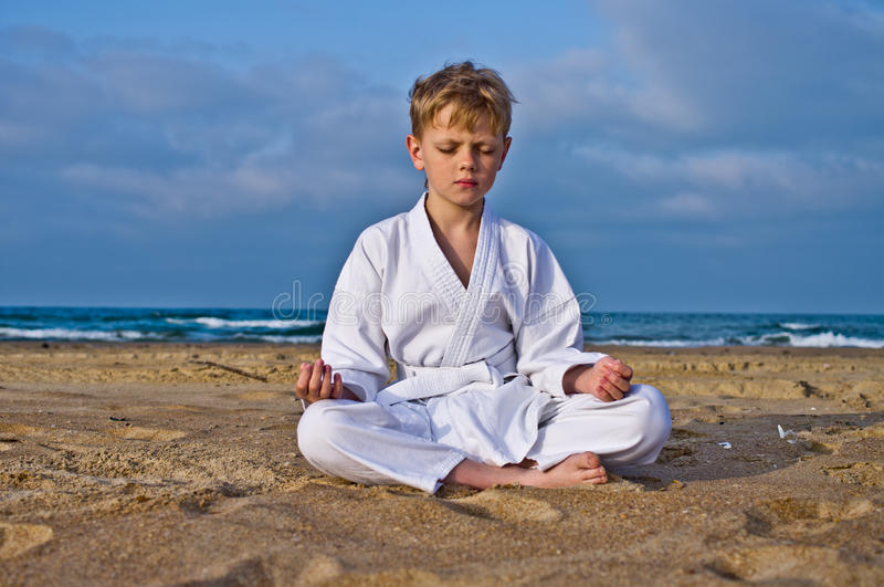 O menino do karaté meditates fotografia de stock royalty free
