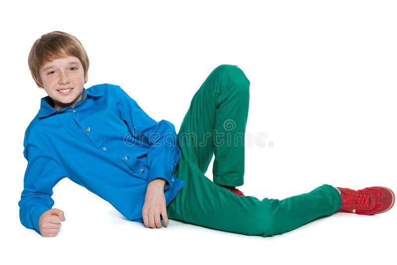 O menino do Preteen está encontrando-se no fundo branco imagens de stock royalty free