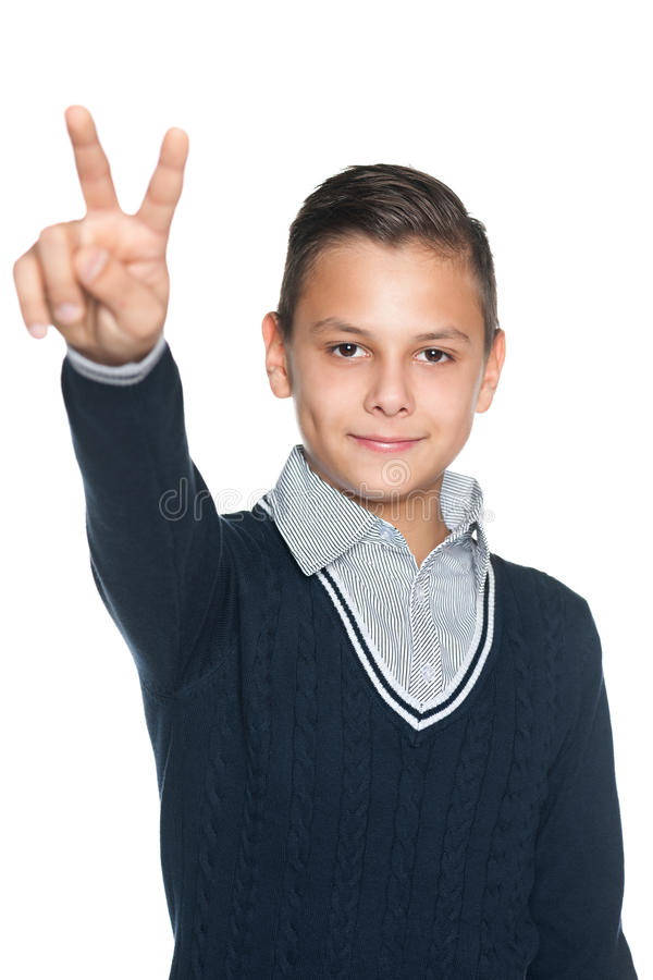 O menino do Preteen mostra o sinal da vitória fotos de stock