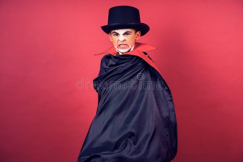 O menino do vampiro de Dia das Bruxas acena seu casaco preto, vermelho com suas mãos cercadas no fundo vermelho do estúdio imagem de stock royalty free