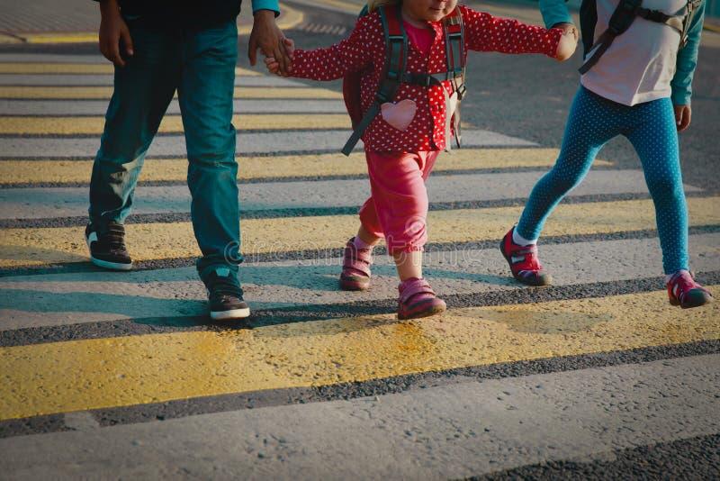 O menino e as meninas que guardam as mãos vão educar o cruzamento a estrada imagens de stock