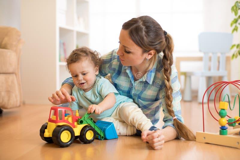 O menino e a mamã da criança pequena jogam no assoalho com brinquedo do trator fotografia de stock
