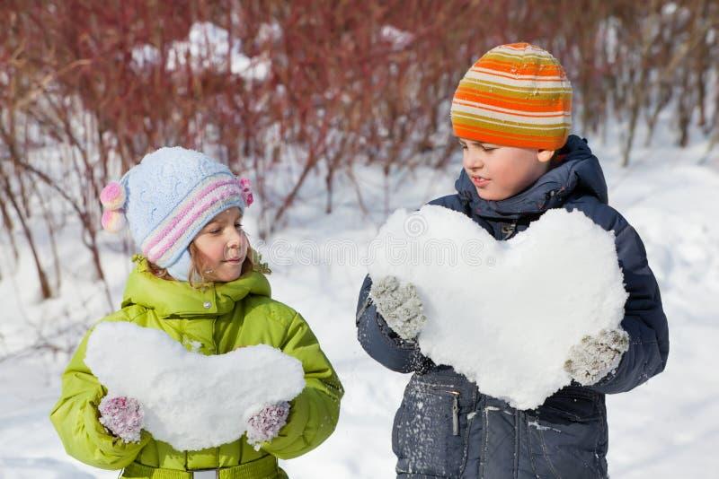 O menino e a menina do adolescente mantêm corações da neve imagens de stock