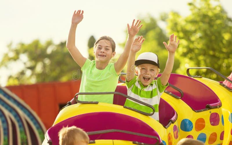 O menino e a menina em uma montanha russa de excitação montam em um parque de diversões fotos de stock