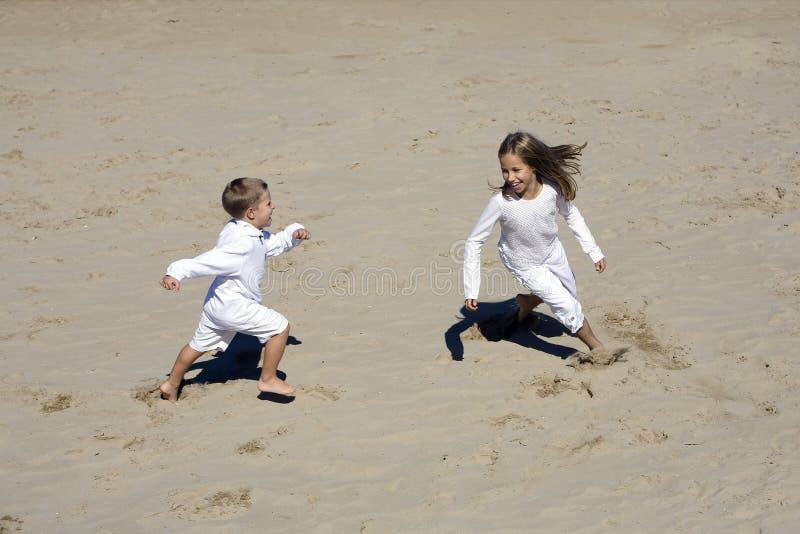O menino e a menina jogam junto na praia fotos de stock