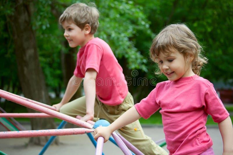 O menino e a menina jogam um campo de jogos das crianças fotos de stock