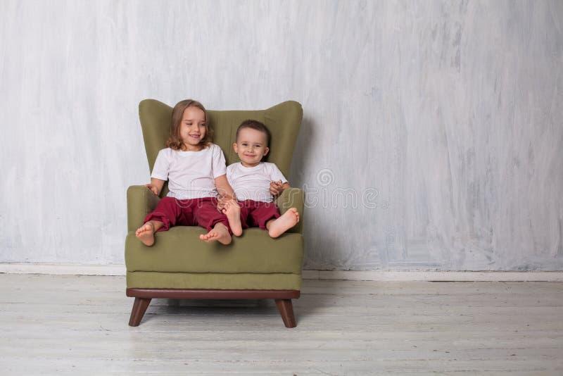 O menino e a menina são irmão e a irmã senta-se em um sofá verde na sala imagem de stock royalty free