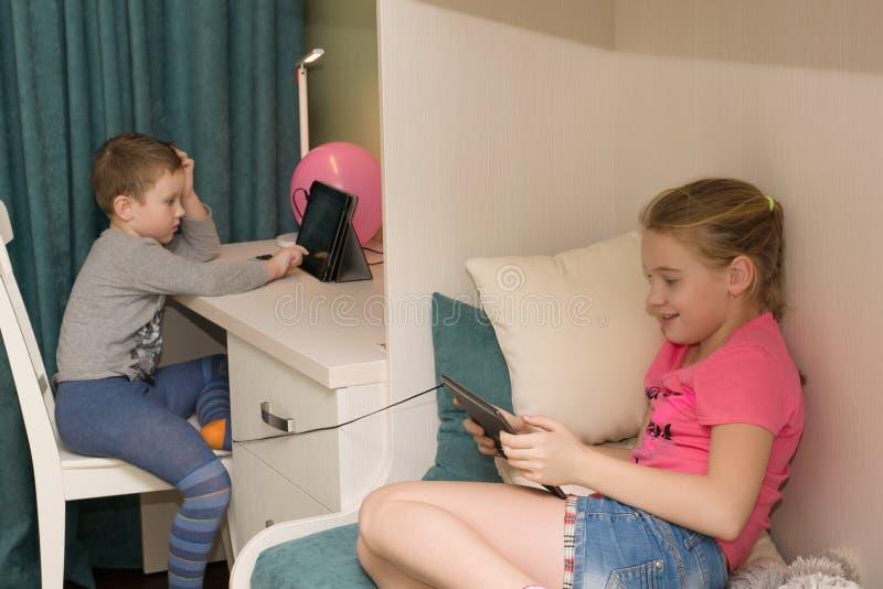 O menino e a menina sentam-se nos computadores foto de stock royalty free