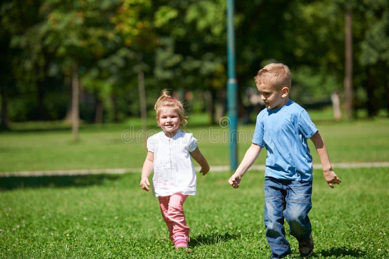 O menino e a menina têm o divertimento e o corredor no parque fotos de stock