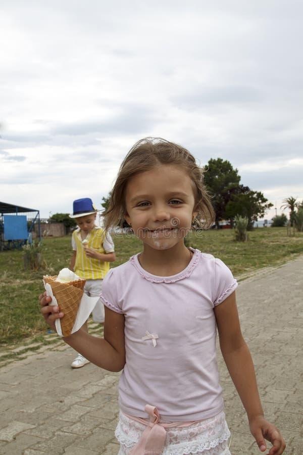 o menino e a menina v?o comer o gelado em f?rias imagens de stock