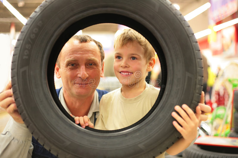 O menino e o homem olham no pneu do veículo imagem de stock