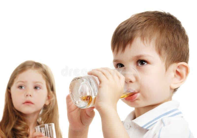 O menino e o suco da bebida da menina imagens de stock royalty free