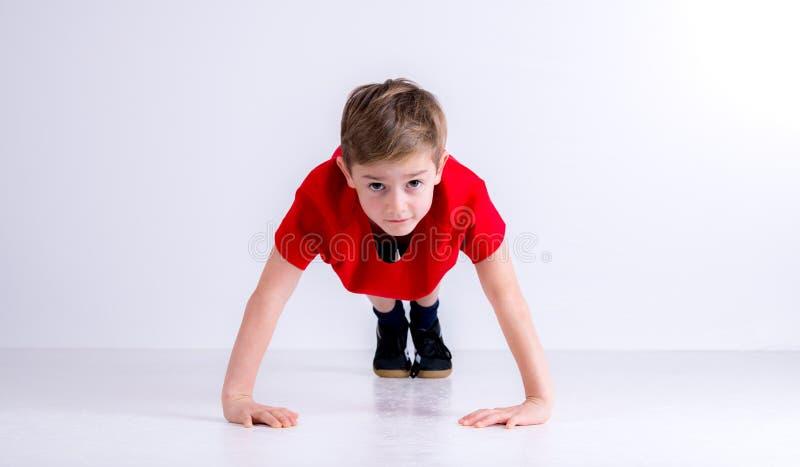 O menino em fazer vermelho da camisa empurra levanta fotografia de stock royalty free