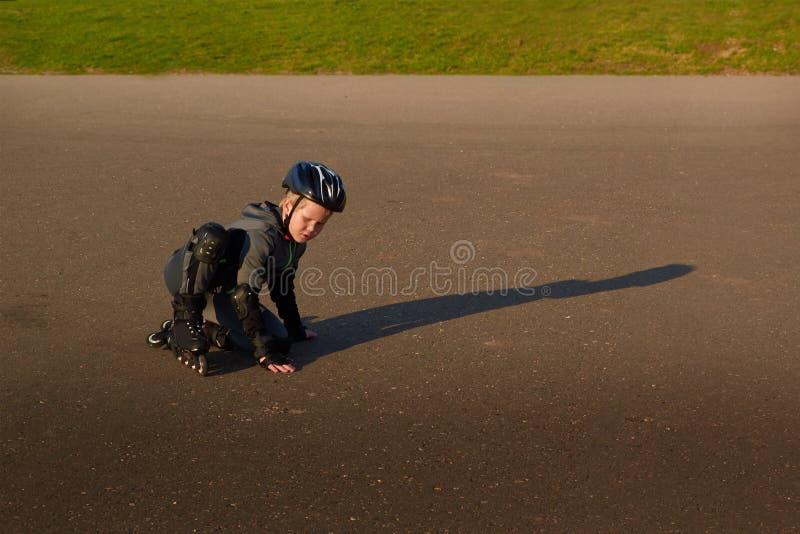 O menino em patins de rolo levanta-se após a queda imagens de stock
