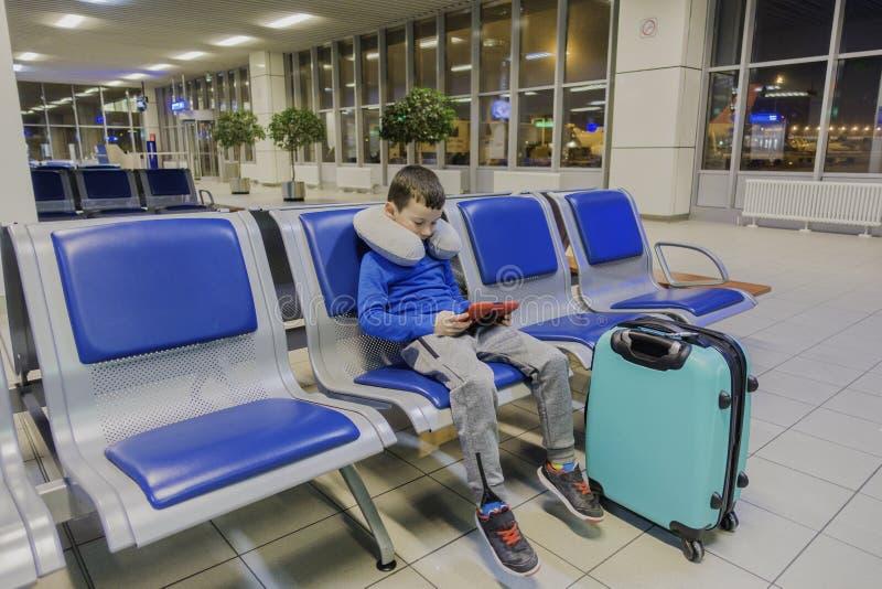 O menino em um aeroporto vazio um espera o plano e os jogos em seu dispositivo favorito imagem de stock royalty free