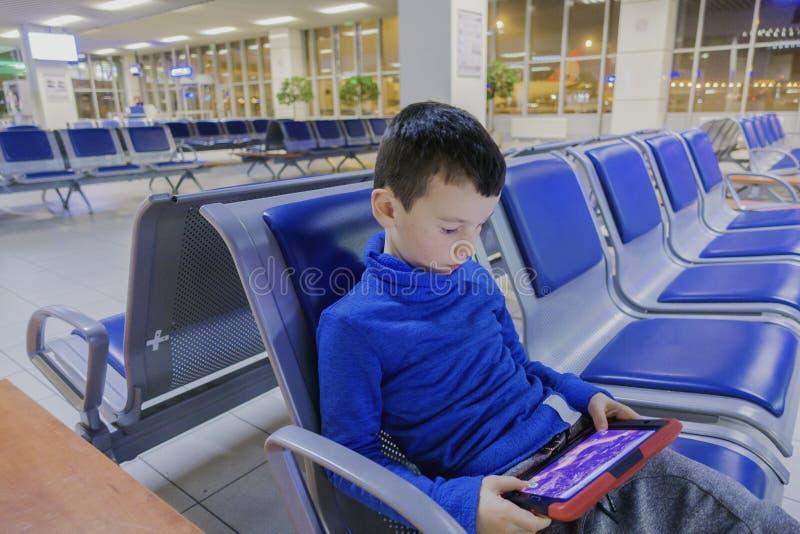 O menino em um aeroporto vazio um espera o plano e os jogos em seu dispositivo favorito imagem de stock