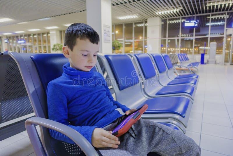 O menino em um aeroporto vazio um espera o plano e os jogos em seu dispositivo favorito fotografia de stock
