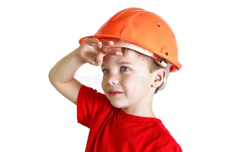O menino em um capacete olha na distância fotos de stock royalty free