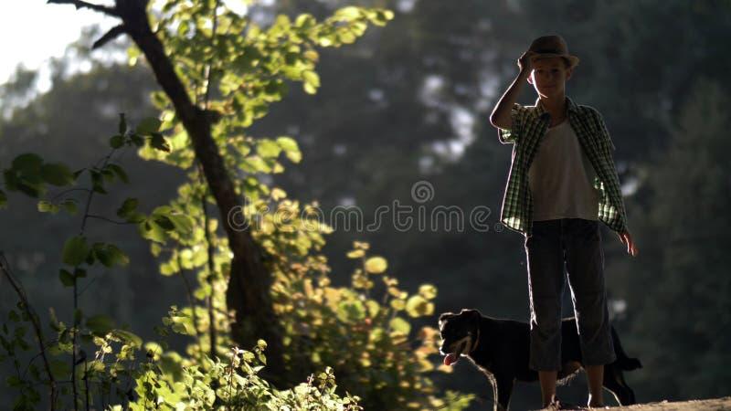 O menino em um chapéu tem o divertimento com um cão fora fotos de stock