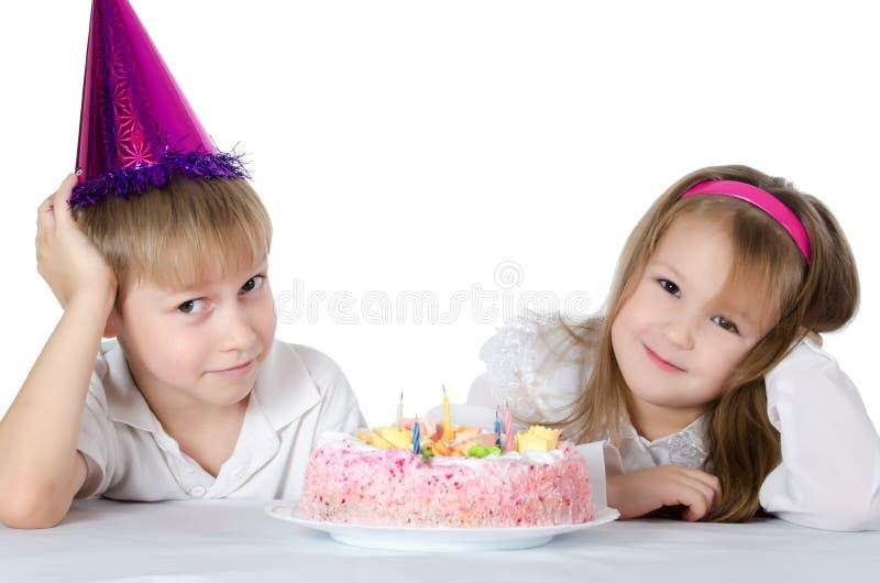 O menino em um tampão com uma torta fotos de stock