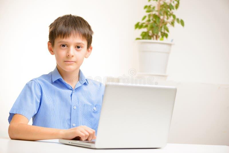 O menino em uma camisa azul usa um portátil que senta-se dentro em uma tabela fotos de stock