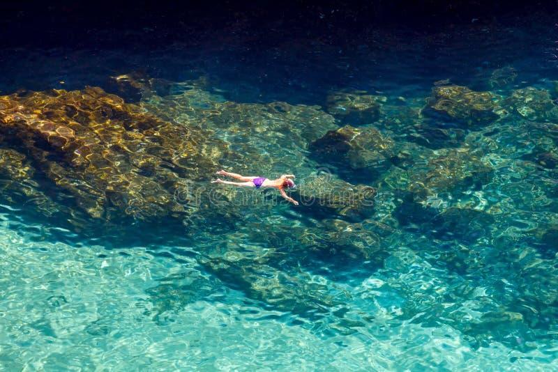 O menino em uma máscara flutua no mar imagens de stock