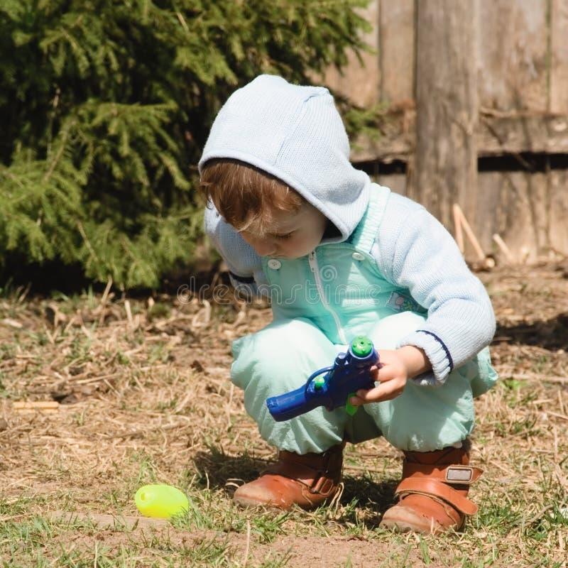 O menino em uma pele-árvore joga um brinquedo da cor (3) imagens de stock