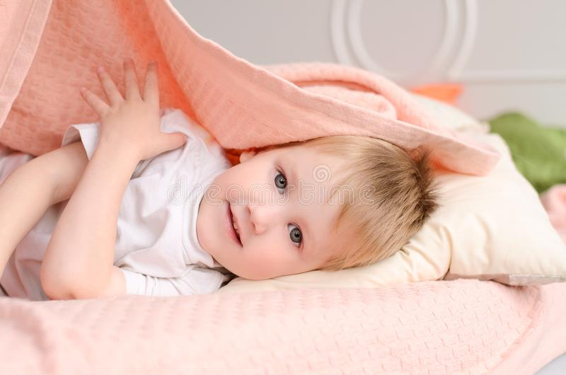 o menino encontra-se em uma cama sob uma cobertura foto de stock
