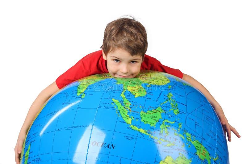 O menino encontra-se no globo inflável isolado no branco imagens de stock