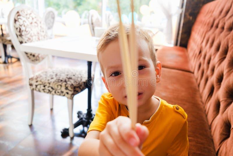 O menino engraçado pequeno come rolos tradicionais japoneses com os hashis, comendo o sushi imagens de stock royalty free