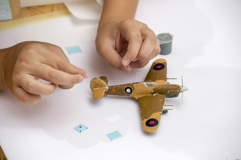O menino entrega a revestimento o jogo modelo plástico dos aviões ww2 fotografia de stock royalty free