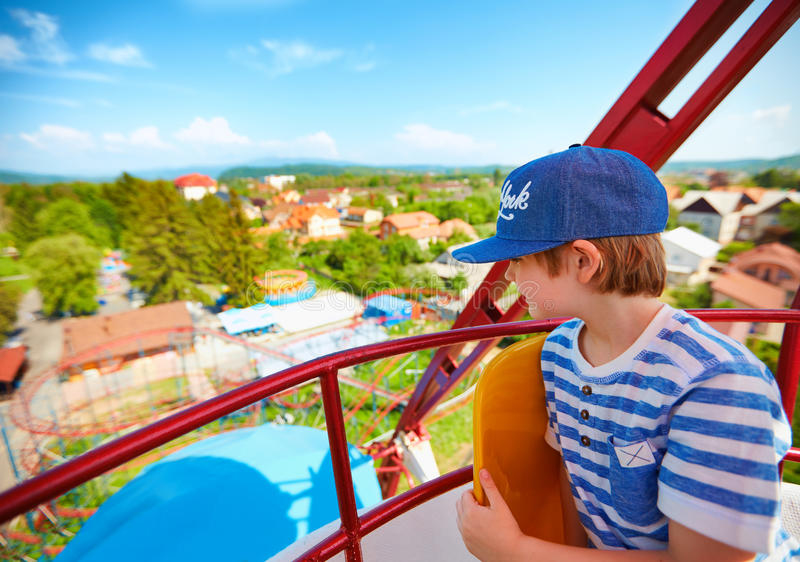 O menino entusiasmado que aprecia a vista dos ferris roda dentro o parque de diversões imagem de stock