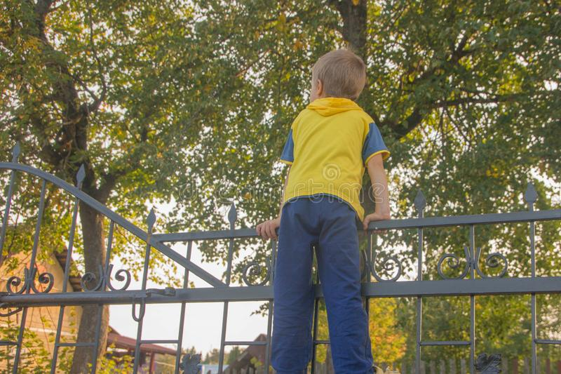 O menino escalou na cerca A criança escala na porta, fe fotografia de stock