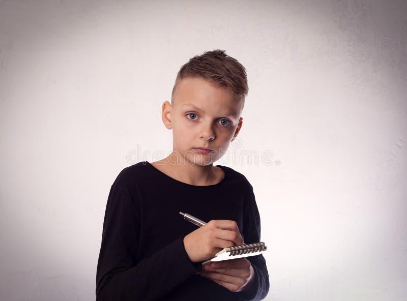 O menino escreve no caderno, conceito da educação foto de stock royalty free