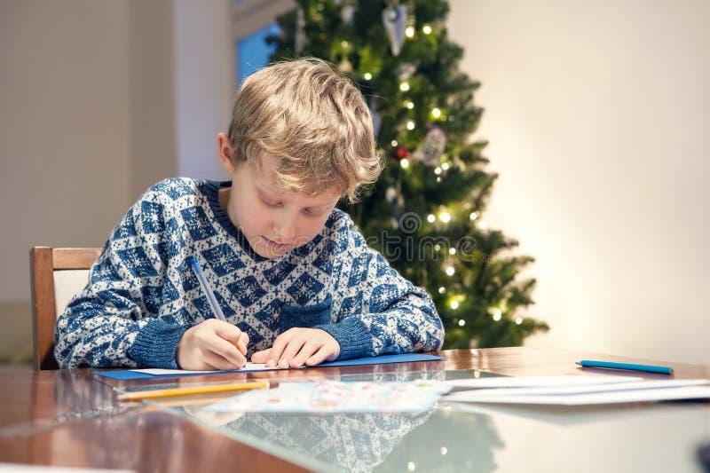 O menino escreve o cartão de Natal das felicitações foto de stock royalty free