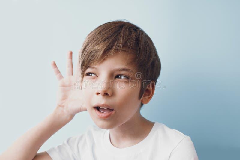 O menino escuta atentamente, levantando sua mão sua orelha fotos de stock royalty free