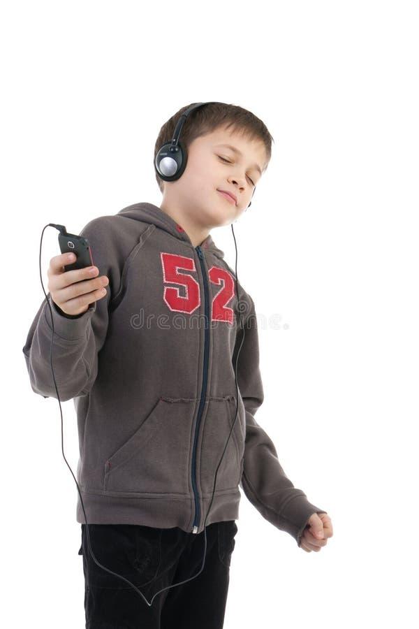 O menino escuta a música foto de stock