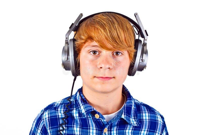 O menino escuta a música com seus fones de ouvido imagem de stock