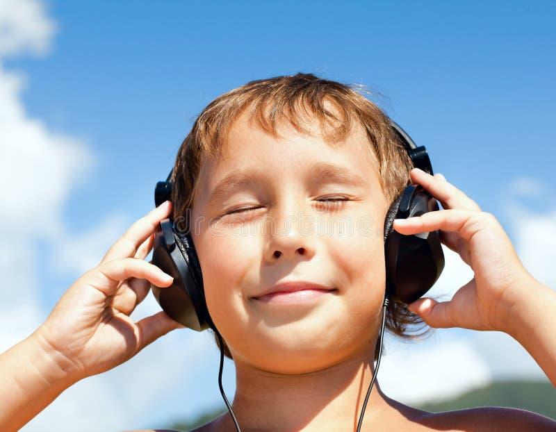O menino escuta a música em auscultadores fotografia de stock