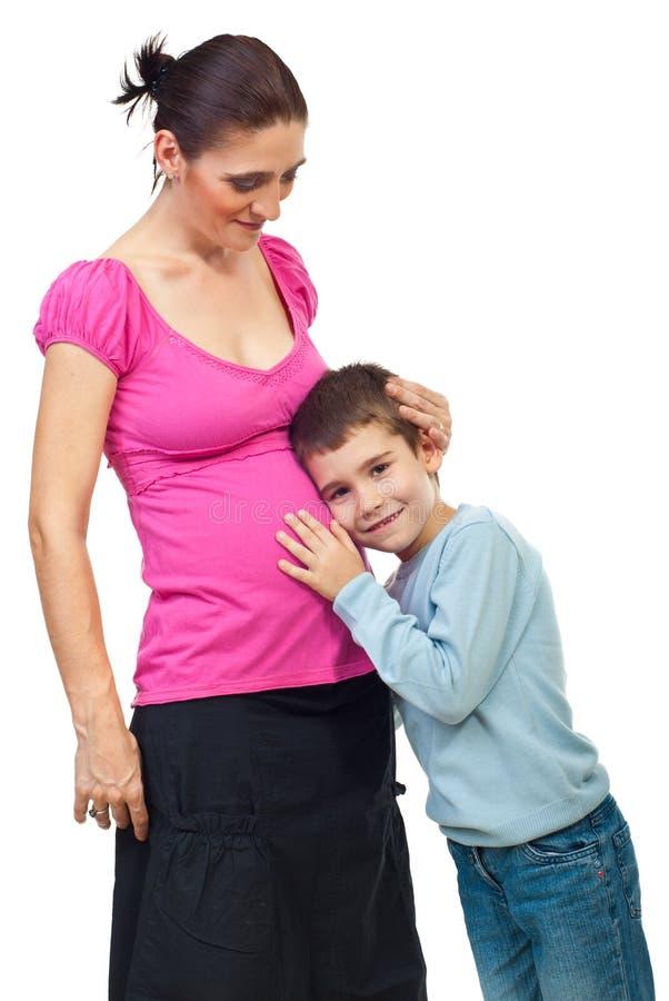 O menino escuta sua barriga grávida da matriz fotografia de stock royalty free